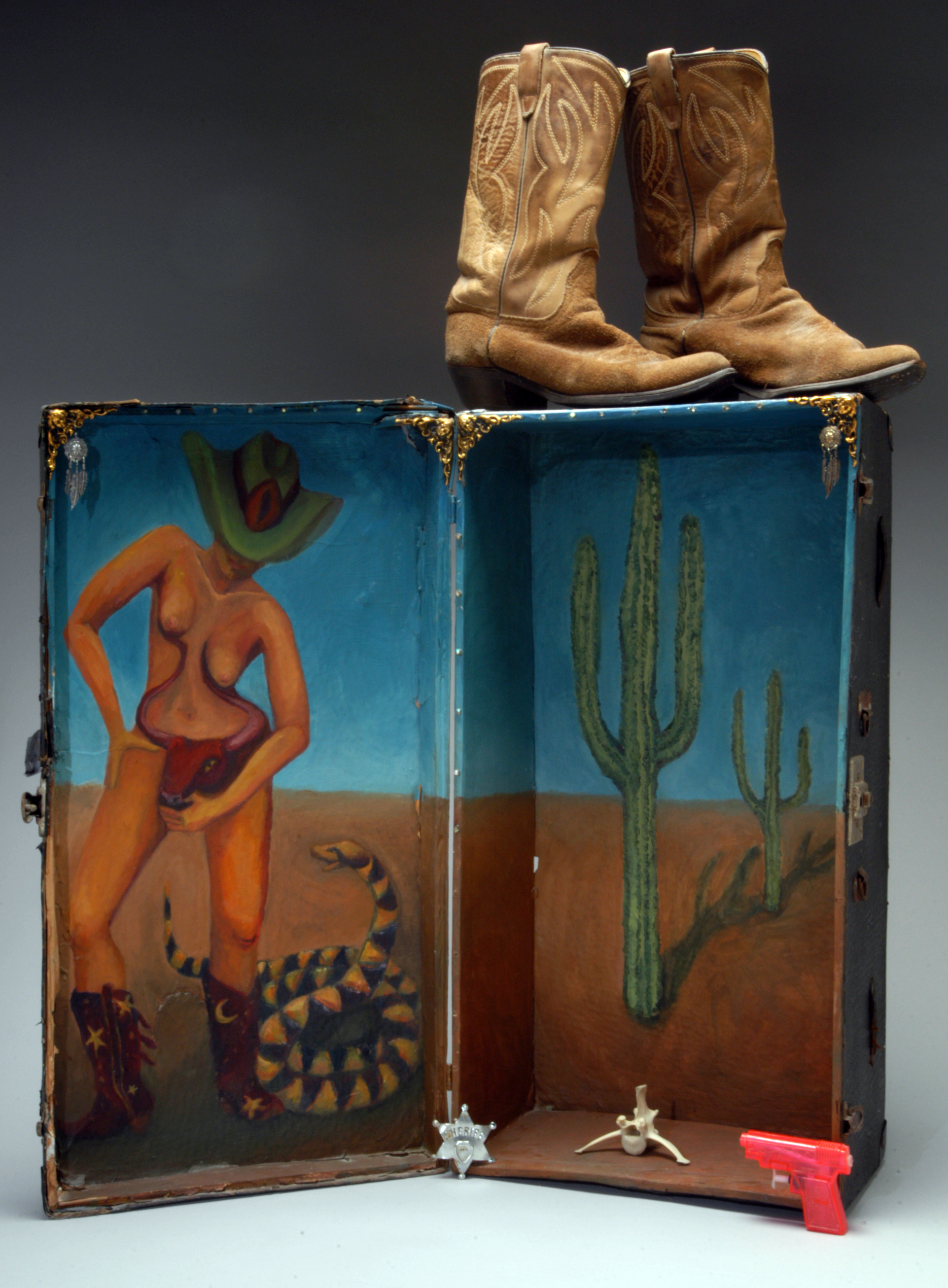 "Bulldyke (Wide Open Spaces), 1992 Oil on trunk, sheriff's badge, bones, squirt gun, boots, 28"" h x 26"" w x7"" deep, Eleanor Ruckman"